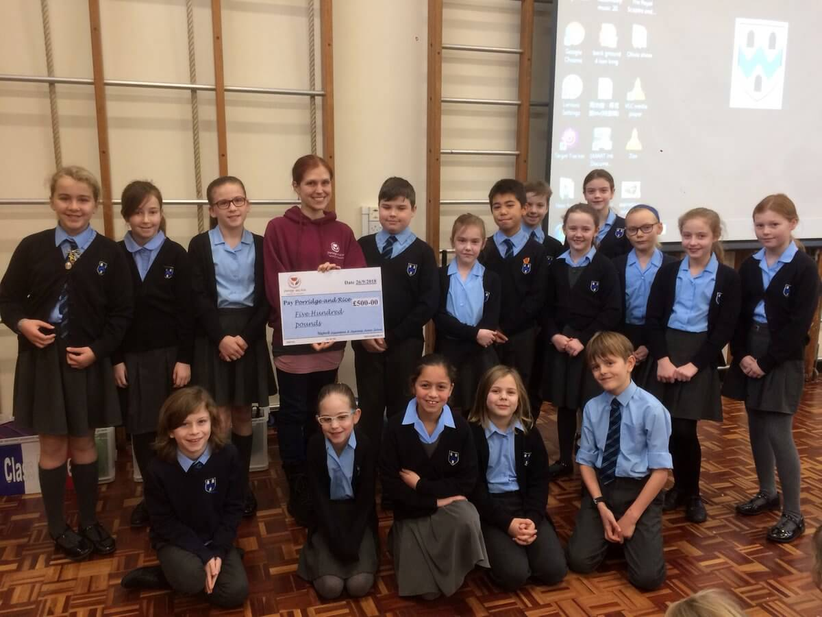 Emma Ballinger, vice-chair of the charity Porridge and Rice accepts a cheque from the school