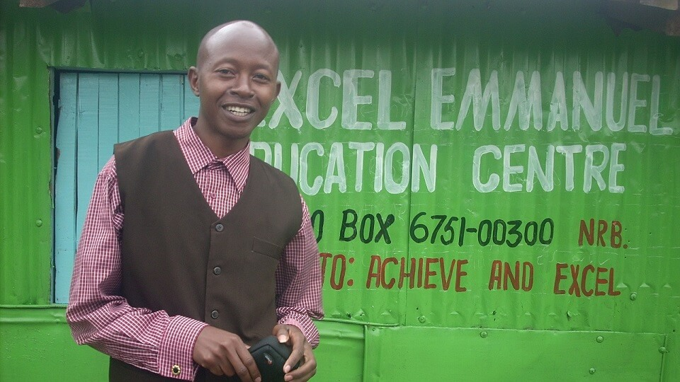 Titus, head teacher of Excel school, outside a newly painted school building