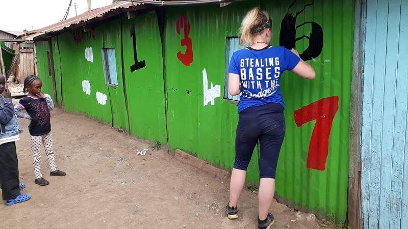 Izzy, a Porridge and Rice volunteer from Liverpool, helps to paint Excel school in the Nairobi slums