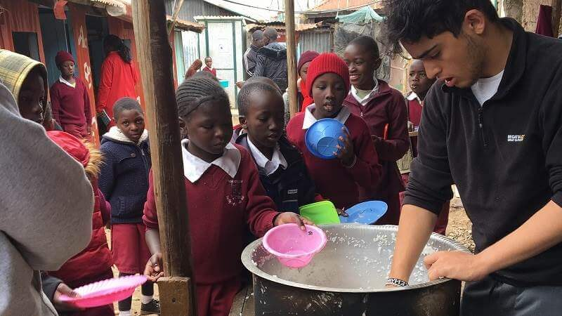 John, a volunteer with Porridge and Rice, helps to serve meals at Lizpal school in Ngando