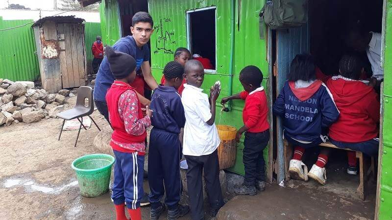 George, a Porridge and Rice volunteer from London, reminds children to wash their hands before meals