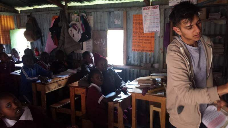 Jai, an A level student and volunteer with Porridge and Rice, teaches a maths class at a Porridge and Rice school in Ngando