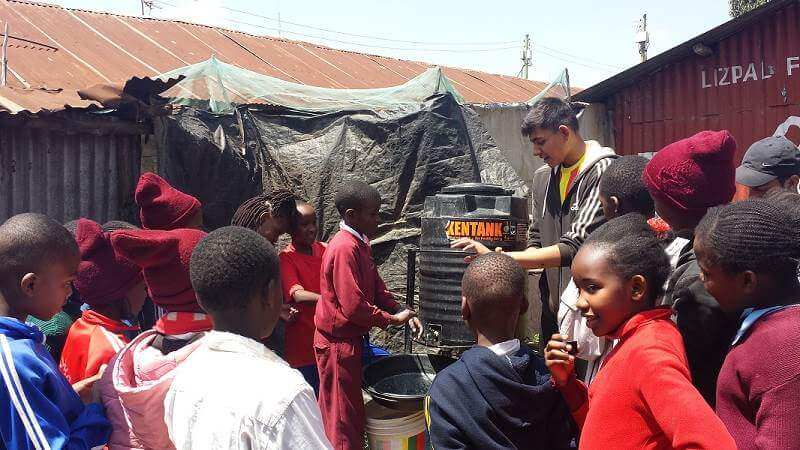 Jay, a volunteer with Porridge and Rice during his A level year, works with children to make sure they wash their hands properly