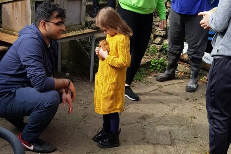 Mohit assist a young girl to hold a baby guinea pig at the petting day for Porridge and Rice